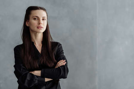 Business portrait of young confident woman looking at camera, crossed hand on chest, standing against copy space wall. Successful businesswoman in formal wear on gray background