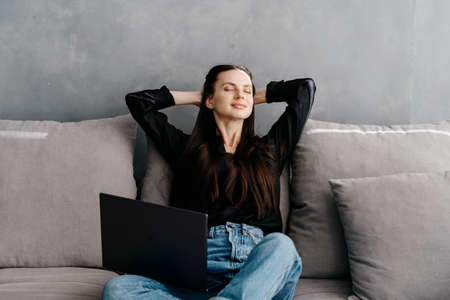 Concept of rest and work from home. Young dreamy woman sitting on sofa in living room, holding hands behind head, closed eyes, enjoying moment. Serene and peaceful female with laptop smiling calm Stock Photo