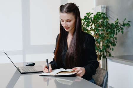 Remote work and home office concept. Young and busy business woman sitting behind table near modern laptop computer, writing notes in agenda, makes a strategy plan for the new startup