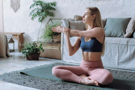 Side view of beautiful young adult woman in sportswear stretching arms, warming up her body and making sport training at home, Female sitting on exercise mat in apartment with cozy living room
