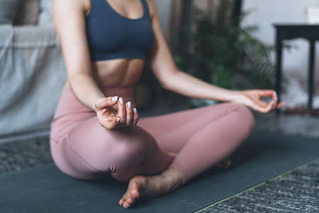 Wellness and well-being concept. Cropped view of sporty and healthy woman practicing yoga, sitting in half lotus meditation pose, doing ardha padmasana exercise, close up hands with mudra gesture