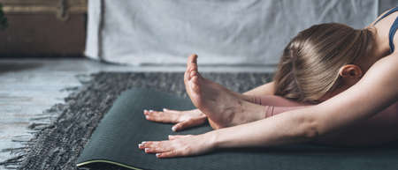 Cropped shot of woman stretching body in seated forward bend position, doing yoga on mat at home, panoramic sports banner. Active lifestyle and wellbeing concept 免版税图像