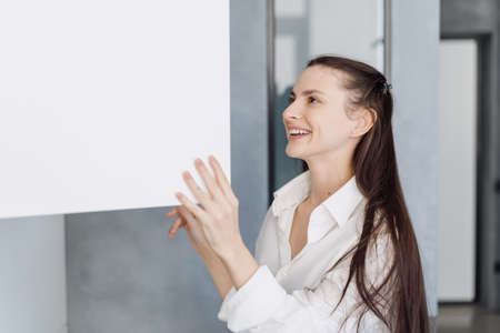 Happy young woman in homewear smiling while opening white cupboard with clean dishware while standing in morning in her modern stylish kitchen at home