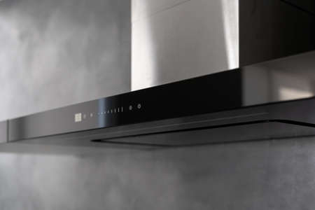 State of art sleek technological black exhaust hood, touch controls marked with white, kitchen appliance in apartment with modern interior, light gray wall in blurred background. Close up shot 免版税图像