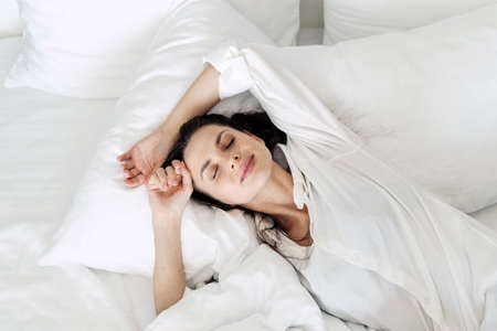 View from above of young sleepy and relaxed brunette woman with closed eyes lying on bed with clean white bedding at home, female waking up and stretching arms after night sleep Standard-Bild