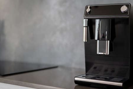 Black coffee making machine with glossy metal parts on shiny kitchen counter next to induction stovetop, pair of control knobs to change modes, blurred background, copy space for text 免版税图像