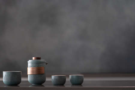 Glossy reflective countertop with nice ceramic blue teapot set, three small cups, brewing tea for guests, healthy and organic drink, gray wall in blurred background with copy space for text