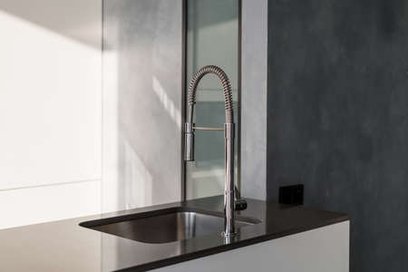 Glossy kitchen counter with long modern metallic shiny faucet and sink with square shape, interior with simple design, room illuminated by light coming from window