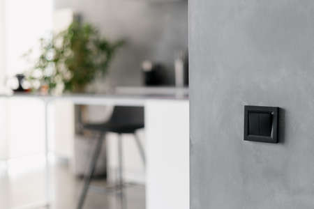 Black light switch on gray wall in modern themed kitchen environment, black bar stool, various home appliances, different white furniture and potted plant in blurred background
