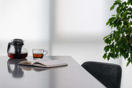 Cozy workplace at home. Open note book lying on table with reflective surface, cup of tea next to teapot, black chair under desk, light coming from behind white curtains, potted greenery in corner 免版税图像