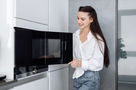 Happy smiling woman in casual outfit opening black microwave door and going to put food in to heat it up while standing in stylish kitchen with white furniture at home 免版税图像