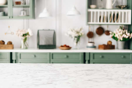 Empty kitchen island with marble surface in foreground, green vintage countertop with drawers and pendant lights hanging above, lots of flowers in jars, blurred background