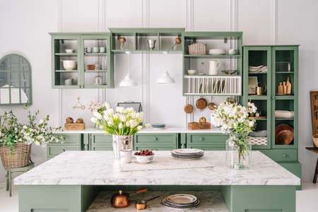 Spacious kitchen with vintage design, counter with marble top and flowers in metal bucket on it, organized furniture with various crockery, comfortable apartment interior Stockfoto