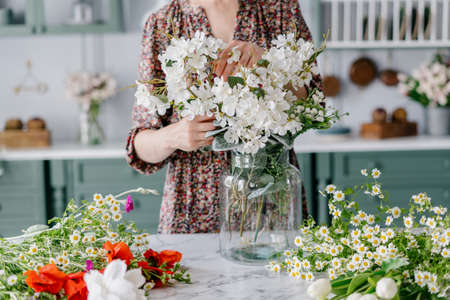 Woman in dress arranging bouquet, putting it in big glass jar, marble kitchen island with lots of different colorful flowers, green vintage furniture in blurred background. Cropped shot