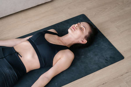 View from above on beautiful young woman lying on yoga mat and meditating with her eyes closed, enjoying meditation practice, feeling relieved and relaxed. Peace, tranquility and mindfulness concept