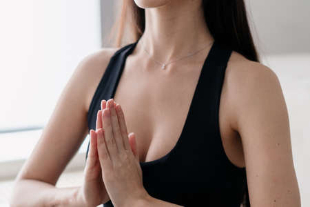 Cropped photo of calm healthy woman putting her hands together in prayer gesture during yoga practice in studio, female meditating at home. Yoga, sport and life balance concept