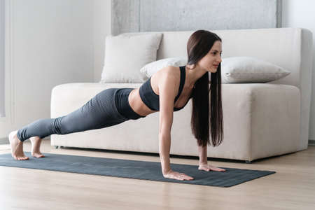 Brunette young woman exercising, standing in plank position to train her abs, arms endurance and strength on yoga mat at home in living room. Healthy lifestyle, fitness and workout concept