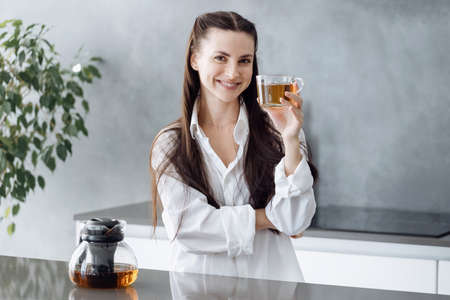 Happy beautiful woman with long brunette hair standing behind countertop and drinking hot tea in glass cup, smiling at camera while standing in modern kitchen, enjoying nice day at home Standard-Bild