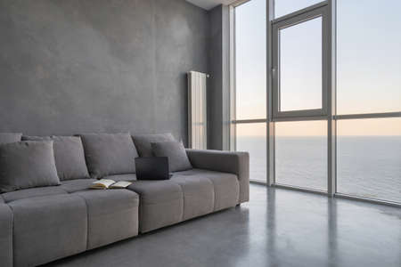 Modern laptop and open planner on gray couch in hotel room. Cozy apartment with loft style interior in home office. Contemporary interior design with new furniture, ocean view from panoramic windows