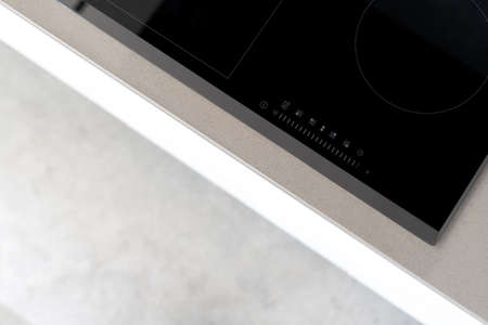 Integrated ceramic induction stove attached to kitchen counter, control panel with marked touch controls to easily adjust heat setting, modern kitchen appliances. Cropped shot Standard-Bild