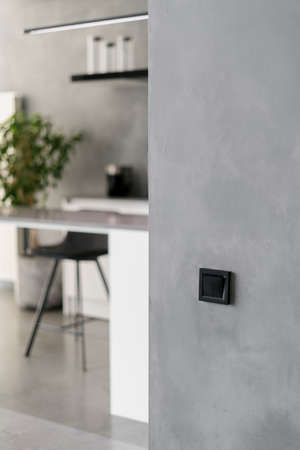 Modern kitchen interior with simple theme, black light switch on gray wall, various furniture and white counter with chair and potted greenery behind it in blurred background. Vertical shot Standard-Bild