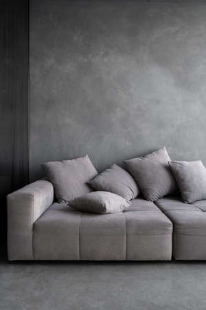 Comfort couch with cushions standing on concrete floor in modern apartment. New sofa at living room with gray copy space wall. Concept of hotel, house and accommodation with loft interior design Standard-Bild