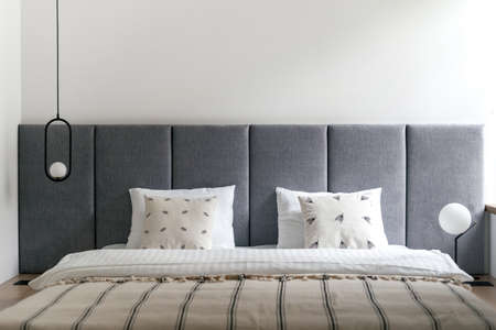 Bedroom interior, bed at modern apartment design. Furniture bedhead with pillows in home. Closeup at cozy scandi room with white bedding decor, blanket. Loft lamp hanging from above.