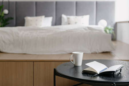 Home bedroom interior, white bed decor. Cozy room with scandinavian design, closeup at coffee table near white bed. Furniture for comfortable relaxation, apartment with wooden object. Standard-Bild