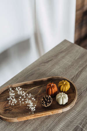 Small round wooden tray laying on top of furniture, pumpkin candles with different colors, simple design, pine cone next to dry plant, white wall in blurred background, copyspace
