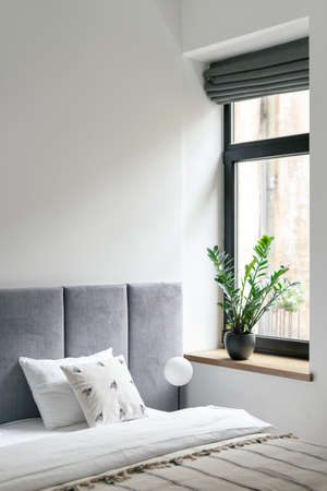 Nobody at bedroom interior, modern home design. Bed near window, comfortable house furniture for apartment decor. Scandinavian minimal style of cozy room with natural light. Standard-Bild