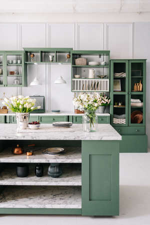 Kitchen with green vintage furniture, marble countertop with flowers and bowl of cherries, bucket with tulips, cupboard with various mugs, crockery and devices. Vertical shot