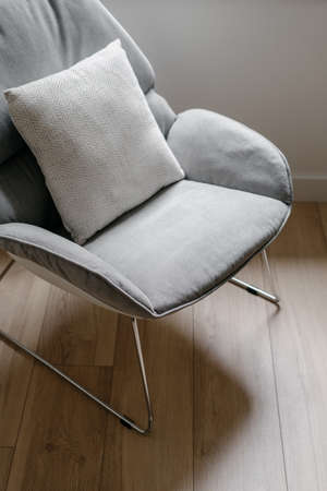 Closeup at interior object, design of home style. Vertical shot of furniture at living room floor. Modern minimalistic house decor with comfortable chair. Nobody at contemporary apartment.