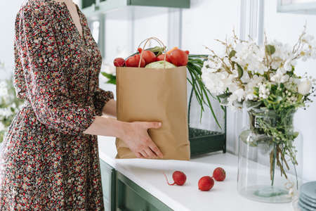 Cropped shot of woman putting paper grocery bag filled with vegetables on countertop in kitchen with white theme and green monochrome furniture, flowers in glass jar