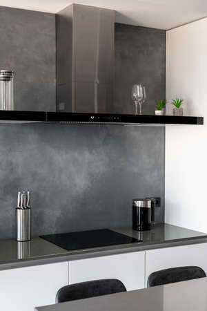 Contemporary clean kitchen with glossy furniture, countertop with black chairs next to it, black induction cooktop with exhaust hood above it, useful technology and home appliances. Vertical shot