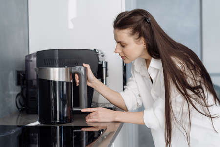 Young beautiful woman with long brunette hair in white nightie using electrical kettle to boil water for morning coffee while standing in fully furnished kitchen after waking up at home
