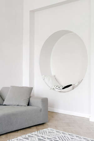 Living room interior, home design in white. Modern apartment style, minimal decor in house. Cozy flat with nobody. White wall with circle niche with pillows, space for relax. Standard-Bild