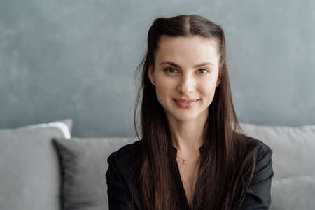 Portrait of young charming brunette woman looking at camera with smile while sitting on couch and spending great time at home, headshot of beautiful friendly female indoors