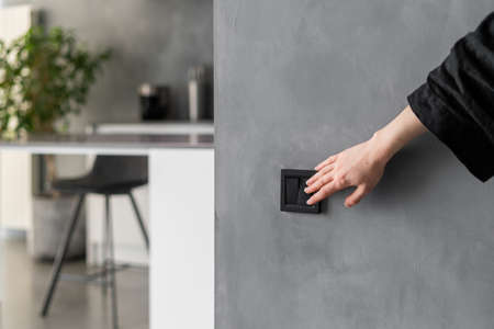 Cropped shot of woman turning light on or off in kitchen using black switch located on gray wall, modern kitchen interior design with plants, furniture and appliances in blurred background