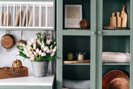 Green vintage cupboard with glass doors, set of various sized wooden cutting boards and tablecloths, countertop with white surface, lots of flowers in metal bucket, comfortable kitchen enviroment Standard-Bild