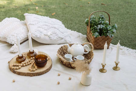 White blanket at green grass, outdoor decor for picnic. Pillows, dishes, wooden decoration at summer park. Closeup at decorative rustic things with nobody outside.