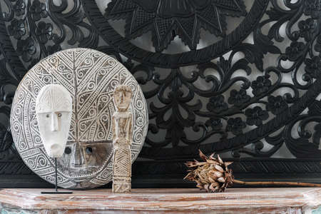 Concept of home decor with natural materials. Close up view of traditional african mask standing on vintage cabinet against black art panel near dry wooden protea flower Standard-Bild