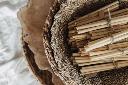 Flat lay view of zero waste and eco-friendly bamboo drink straws lying in wicker basket against white copy space textile. Nature care concept