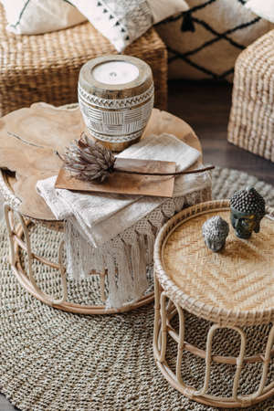 High angle view of home decor, wicker furniture with natural materials stand in bright living room interior at bohemian style. Vertical shot of bamboo table, candle and dry flower in cozy apartment