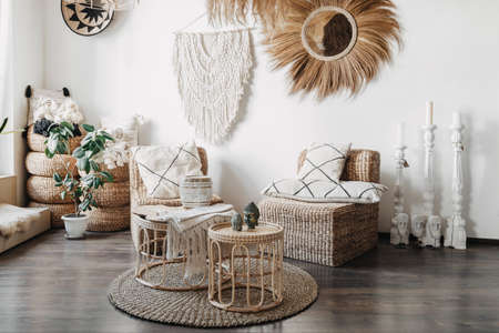 Home decor concept. Comfortable wicker furniture, rattan armchair with cushions, bamboo coffee table and macrame on white wall in cozy living room with ethnic interior design