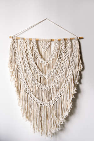 Vertical view of neat handmade macrame hanging on wooden plank at white wall in bright room. Concept of knitting and yarn home decor in boho chic style Standard-Bild