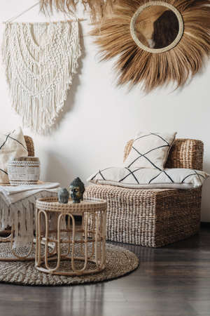 Natural material furniture and macrame on white wall in living room interior in bali or indonesian style. Vertical view of comfortable armchair with cushions near bamboo coffee table with home decor Standard-Bild