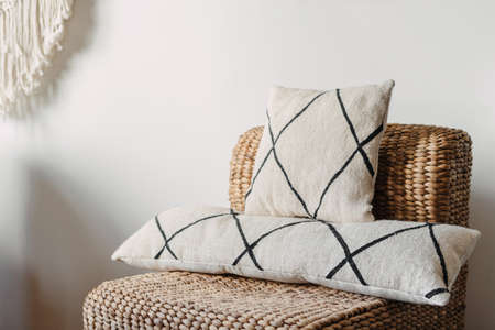 Close up view on soft cushions on comfortable wicker armchair in hygge house. Living room with ethnic boho interior, home decor and rattan furniture against white copy space wall Standard-Bild