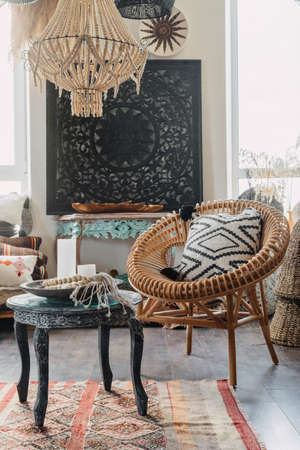 Vertical view of bamboo armchair near wooden coffee table in comfortable living room. Concept of ethnic interior in bali style with indonesian home decor, wicker furniture, soft cushions