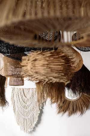 Vertical view of white handmade macrame hanging on wall near assorted wicker lampshade. Concept of showroom with light equipment, home decor and furniture with natural material at bohemian style