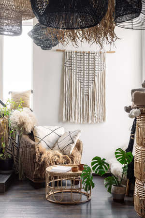 Comfortable living room interior in boho chic style. Vertical view of home decor, natural material furniture, armchair with cushions, bamboo coffee table and macrame on wall under wicker chandelier